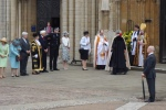 Mulheres de chapeu e bispo aguardam Elizateh II e seu marido