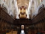 Atrás, vê-se o órgão. Assentos do coro, onde há 900 anos são realizadas as atividades litúrgicas, é todo entalhado em carvalho.